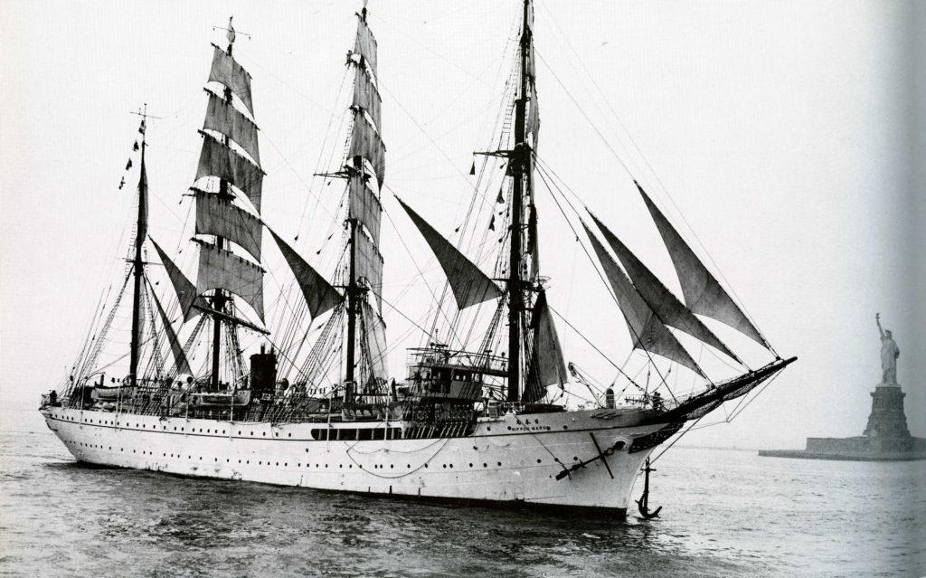 自由の女神の像を背景に帆走する日本丸